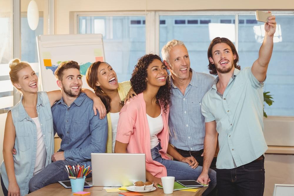 Social Media selfie of colleagues in meeting room at creative office talking tips.jpeg
