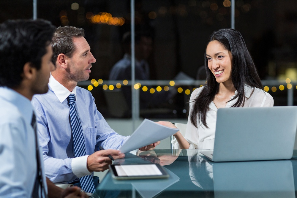 Businesswoman discussing with colleagues in office pay per click advertising leads.jpeg