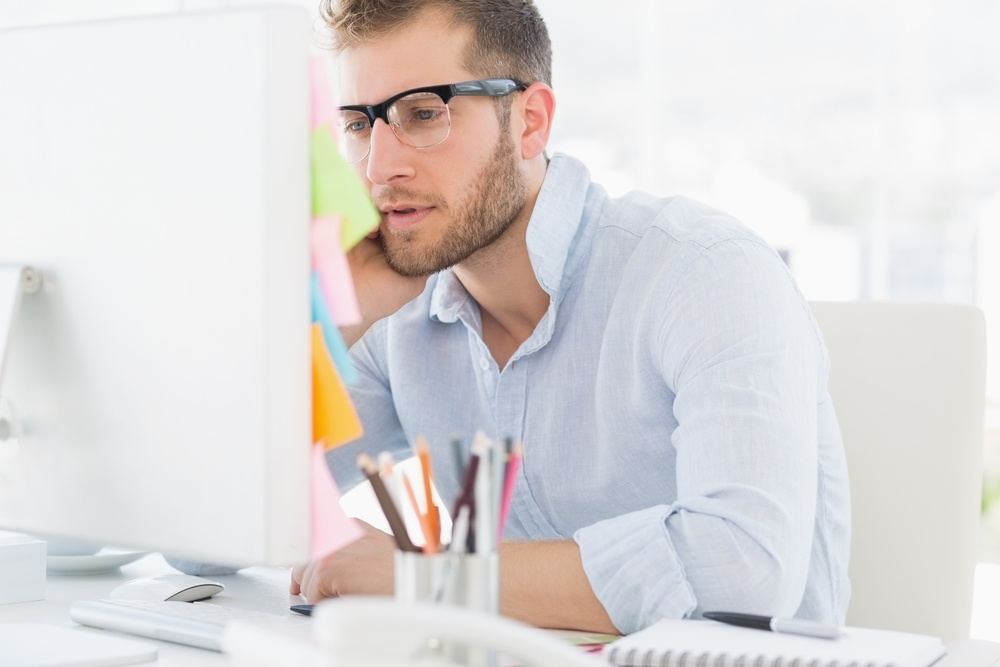 Concentrated young man using computer in a bright office.jpeg