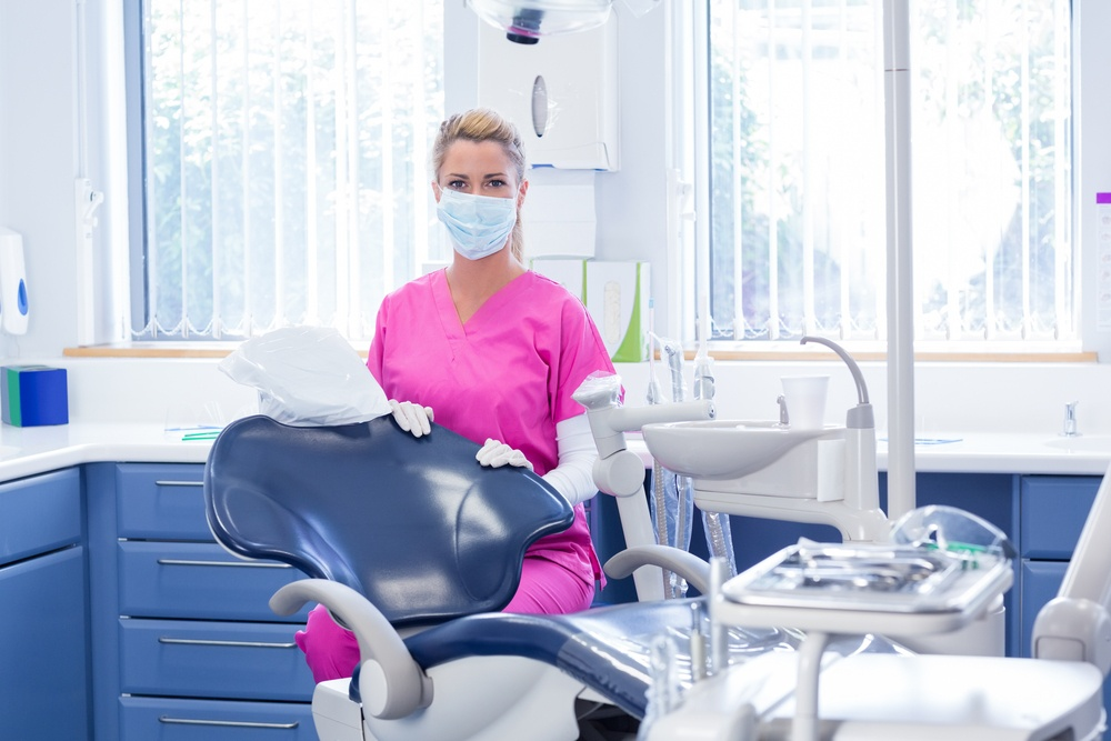 Dentist in mask looking at camera beside chair at the dental clinic.jpeg