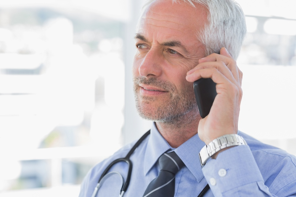 Handsome doctor with mobile phone social paid advertising.jpeg