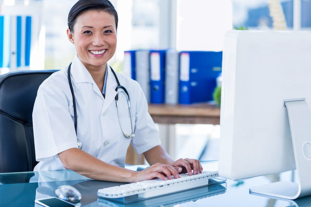 Happy doctor using her computer to stay in touch with patients medical marketing solutions.jpeg