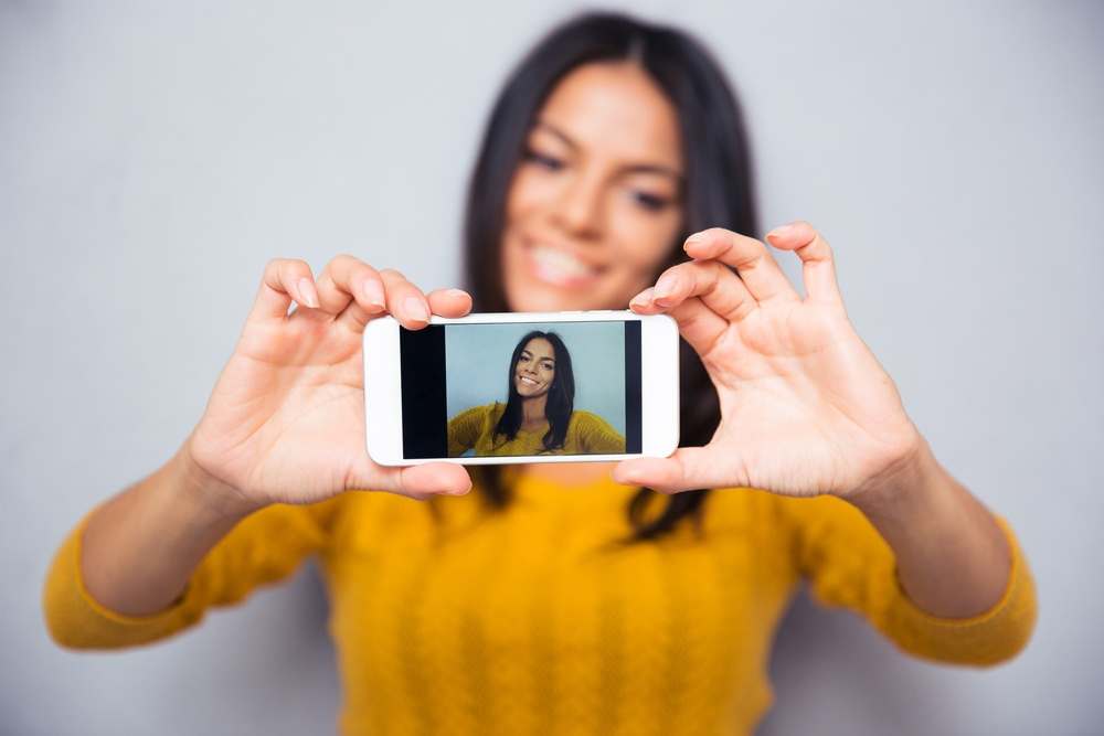 Happy woman influencer making video photo selfie on mobile. Focus on smartphone.jpeg