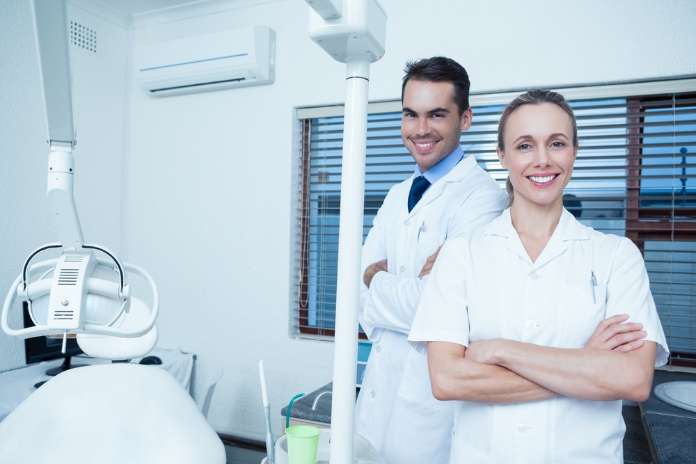 Portrait of smiling male and female dentists blogging medical marketing solutions.jpeg