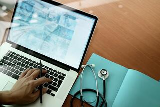 top view of Medicine doctor hand working with modern computer and smart phone on wooden desk inbound marketing email .jpeg